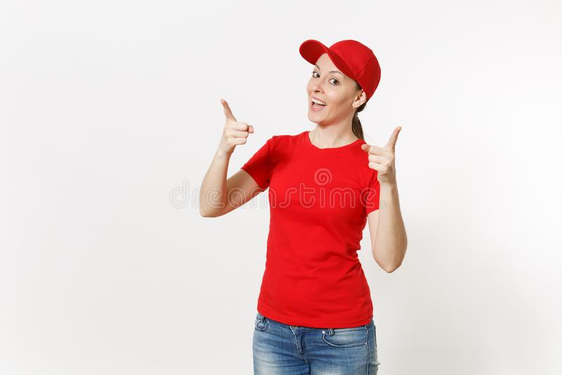 Delivery woman in red uniform isolated on white background. Professional caucasian female in cap, t-shirt, jeans working. As courier or dealer pointing index royalty free stock photo