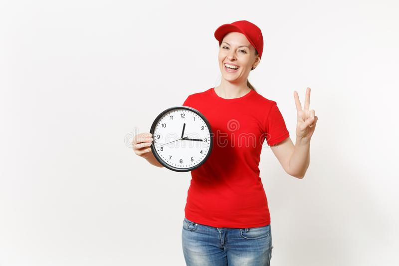 Delivery woman in red uniform isolated on white background. Professional female in cap, t-shirt, jeans working as. Courier or dealer, holding round clock royalty free stock photo