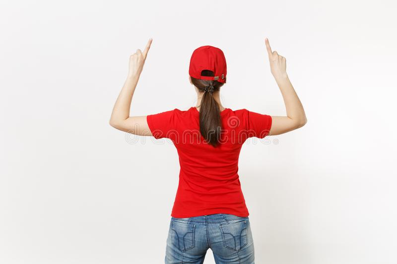 Delivery woman in red uniform isolated on white background. Professional pretty female in cap, t-shirt, jeans working as. Courier or dealer, pointing fingers royalty free stock image