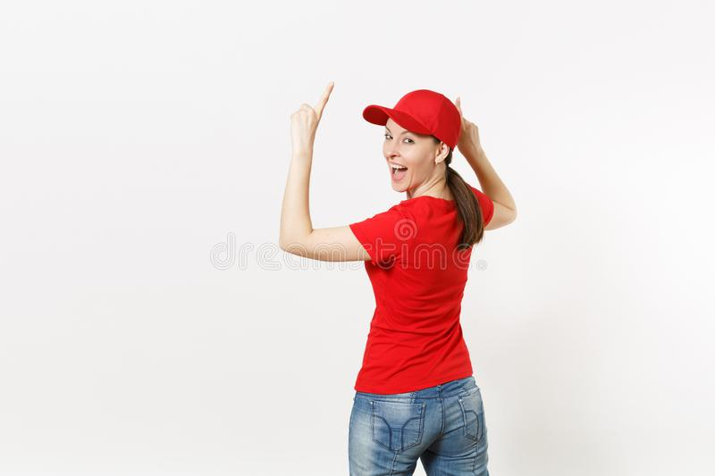 Delivery woman in red uniform isolated on white background. Professional pretty female in cap, t-shirt, jeans working as. Courier or dealer, pointing fingers to royalty free stock images