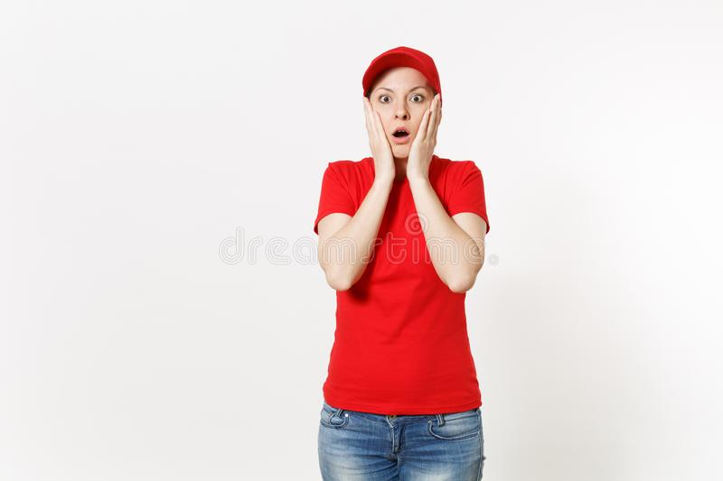 Delivery woman in red uniform isolated on white background. Professional shocked female in cap, t-shirt, jeans working. As courier or dealer, holding hands near royalty free stock images