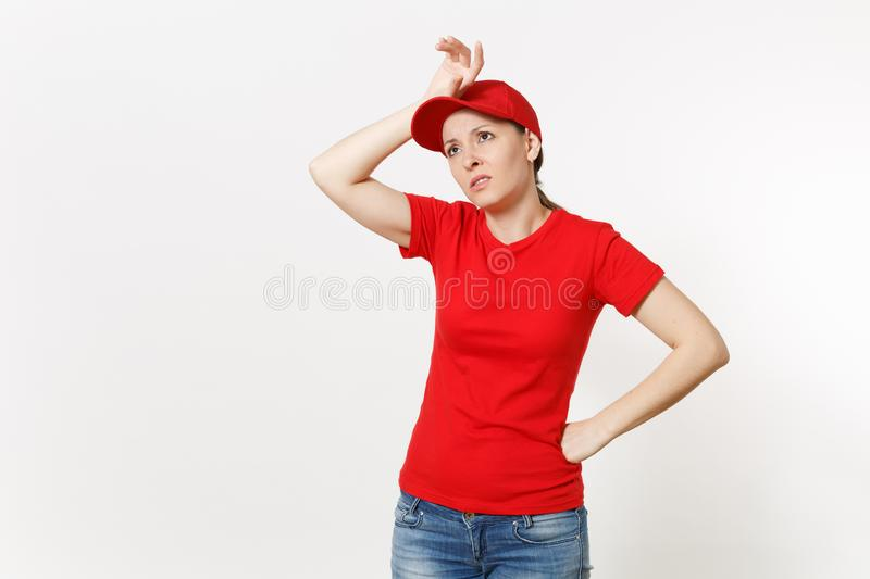 Delivery woman in red uniform isolated on white background. Professional shocked female in cap, t-shirt, jeans working. As courier or dealer, put her hand on stock photo