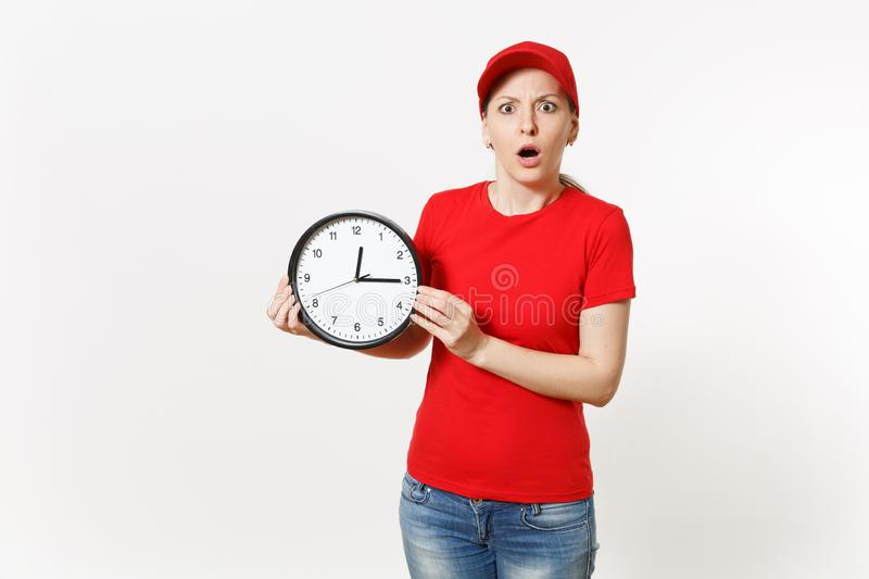Delivery woman in red uniform isolated on white background. Shocked late female in cap, t-shirt, jeans working as. Courier or dealer, holding round clock stock photography