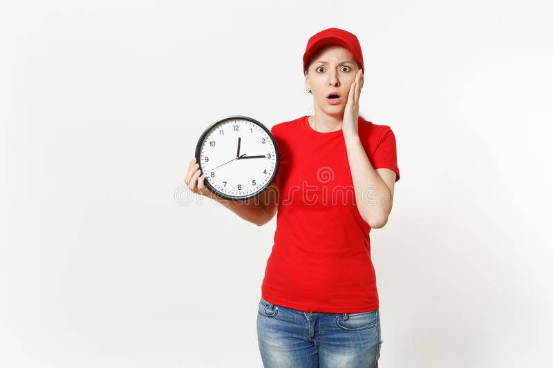 Delivery woman in red uniform isolated on white background. Shocked late female in cap, t-shirt, jeans working as. Courier or dealer, holding round clock royalty free stock photography