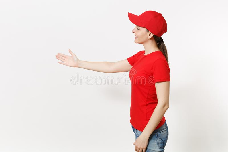 Delivery woman in red uniform isolated on white background side view. Female in cap, t-shirt, jeans working as courier royalty free stock photography