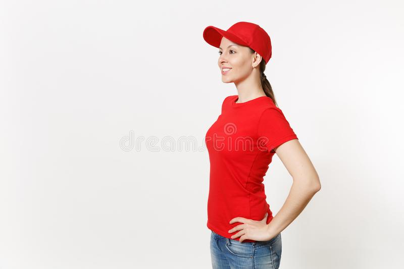 Delivery woman in red uniform isolated on white background side view. Professional female in cap, t-shirt, jeans working. As courier or dealer standing and stock photos