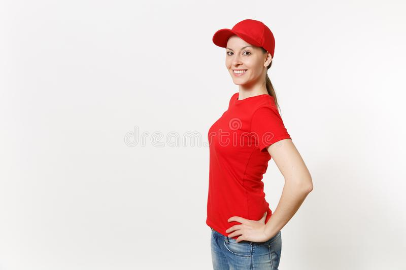 Delivery woman in red uniform isolated on white background side view. Professional female in cap, t-shirt, jeans working. As courier or dealer standing and stock photography