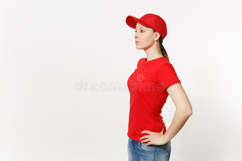 Delivery woman in red uniform isolated on white background side view. Professional female in cap, t-shirt, jeans working. As courier or dealer standing and royalty free stock image