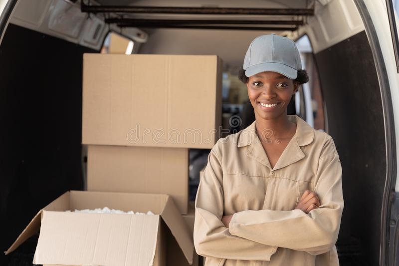Delivery woman standing with arms crossed and looking at camera near van outside the warehouse. Happy delivery woman standing with arms crossed and looking at royalty free stock image