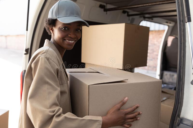 Delivery woman unloading cardboard boxes from a van outside the warehouse. Happy delivery woman unloading cardboard boxes from a van outside the warehouse. This royalty free stock photography