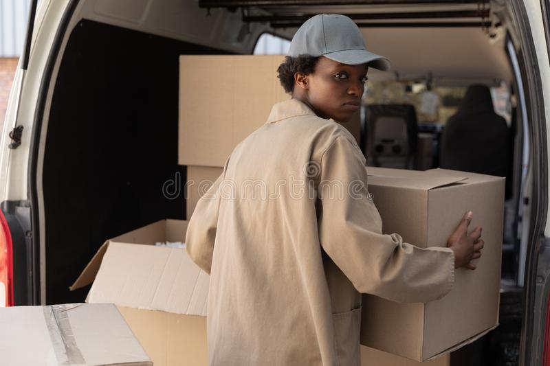 Delivery woman unloading cardboard boxes from a van outside the warehouse stock photography