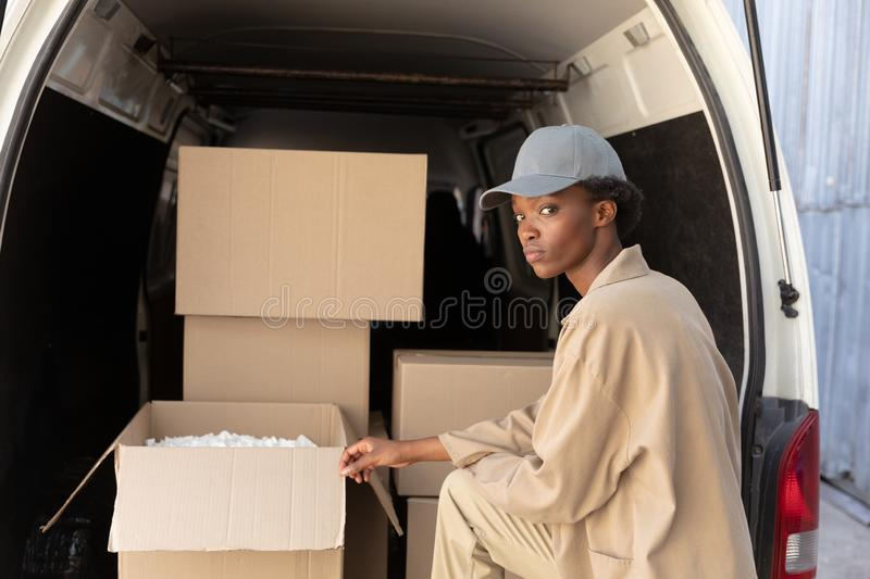 Delivery woman unloading cardboard boxes from a van outside the warehouse. Side view of delivery woman unloading cardboard boxes from a van outside the warehouse stock photos