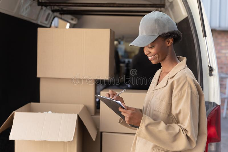 Delivery woman writing on clipboard near van outside the warehouse. Side view of delivery woman writing on clipboard near van outside the warehouse. This is a stock photography
