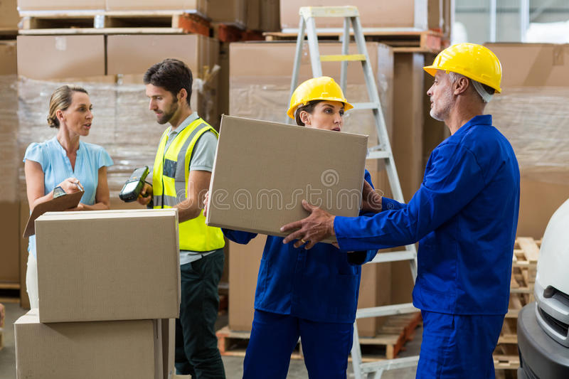 Delivery worker unloading cardboard boxes from pallet jack royalty free stock images