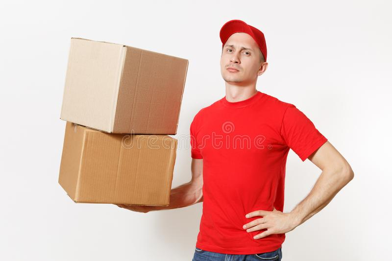 Delivery young man in red uniform isolated on white background. Male in cap, t-shirt, jeans working as courier or dealer. Holding empty cardboard boxes royalty free stock photos