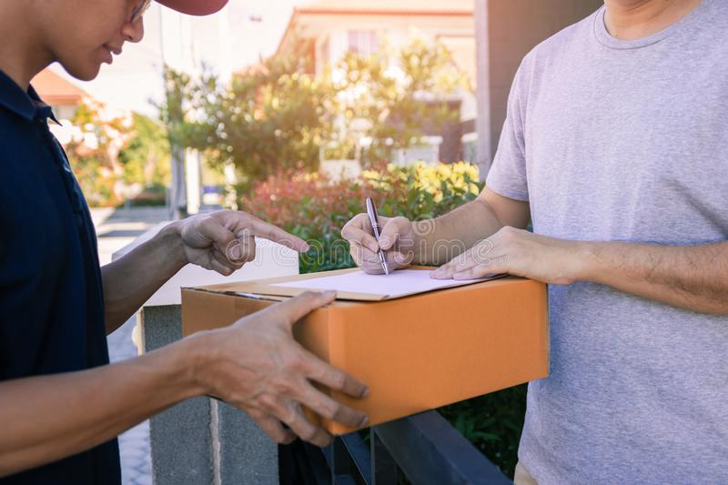 Delivery young man standing at the door of home and carrying parcels for young male to signing stock photo