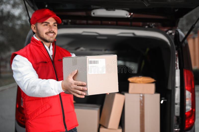 Deliveryman στο ομοιόμορφο δίνοντας δέμα στοκ εικόνες