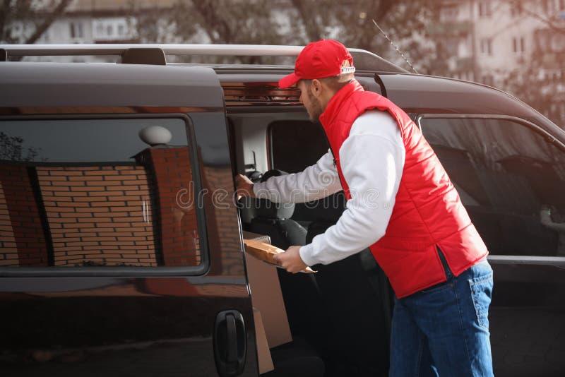Deliveryman στο ομοιόμορφο παίρνοντας δέμα από το φορτηγό στοκ φωτογραφίες