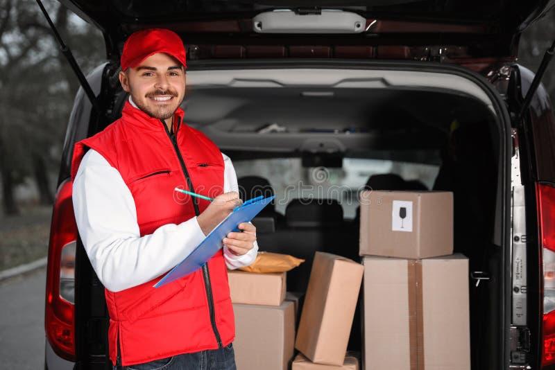 Deliveryman με την περιοχή αποκομμάτων κοντά στο φορτηγό με πολλά δέματα στοκ εικόνες