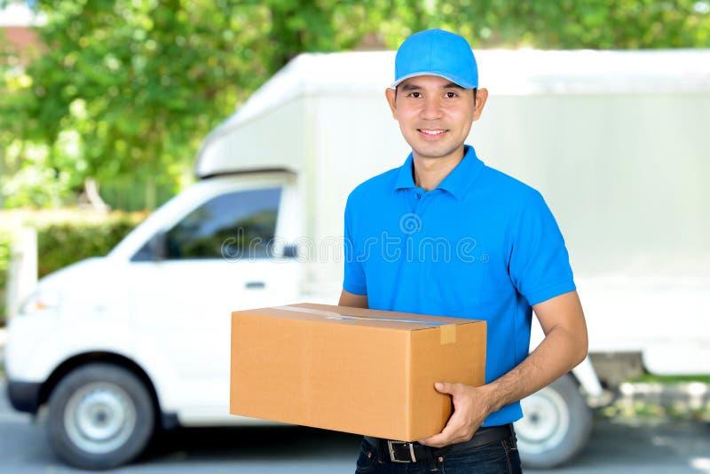 Deliveryman που φέρνει ένα κιβώτιο δεμάτων χαρτονιού στοκ εικόνα με δικαίωμα ελεύθερης χρήσης