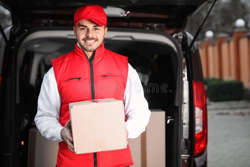 Deliveryman σε ομοιόμορφο με το δέμα κοντά στο φορτηγό στοκ εικόνες