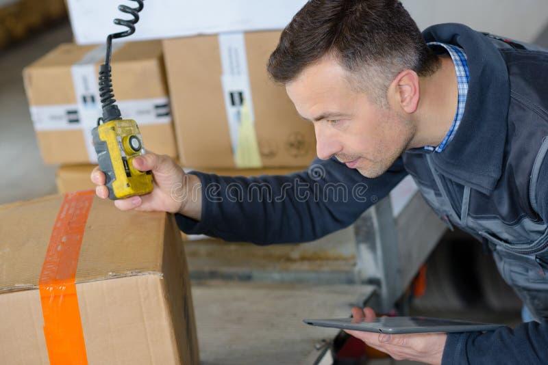 Deliveryman στα κουτιά από χαρτόνι φόρτωσης αποθηκών εμπορευμάτων στο φορτηγό στοκ εικόνα με δικαίωμα ελεύθερης χρήσης