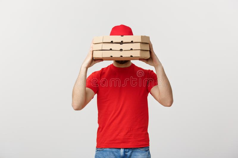 A Deliveryman hidden behind a large stack of pizza boxes he is carrying. Isolated over grey background. royalty free stock image