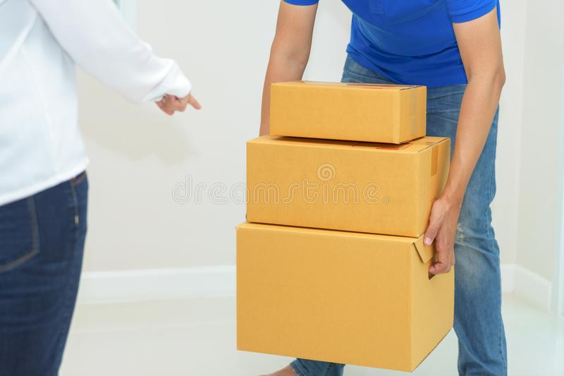 Deliveryman holding boxes into customer home - receiving packag royalty free stock photography