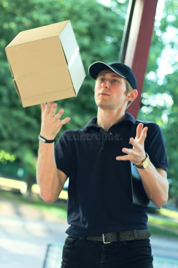 Deliveryman losing a parcel box, in rush. Deliveryman losing a parcel box, in a rush stock photography