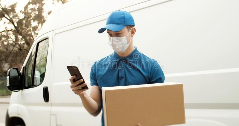 Portrait of young courier in mask standing near car holding carton box using smartphone. royalty free stock photo