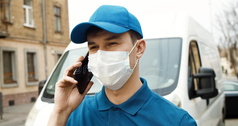 Portrait of young courier in mask standing near car holding carton box using smartphone. royalty free stock images