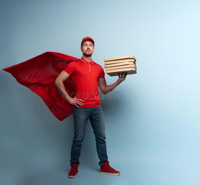 Deliveryman met pizza's doet dienst als een krachtige superheld Begrip succes en garantie bij verzending Studio cyan royalty-vrije stock fotografie