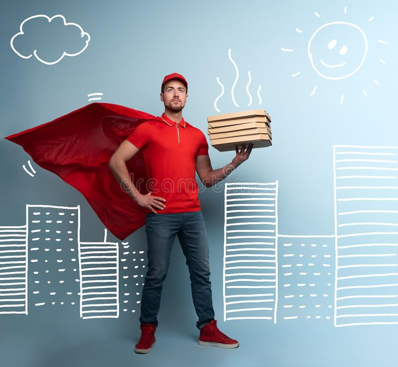 Deliveryman with pizzas acts like a powerful superhero. Concept of success and guarantee on shipment. Studio cyan royalty free stock photos