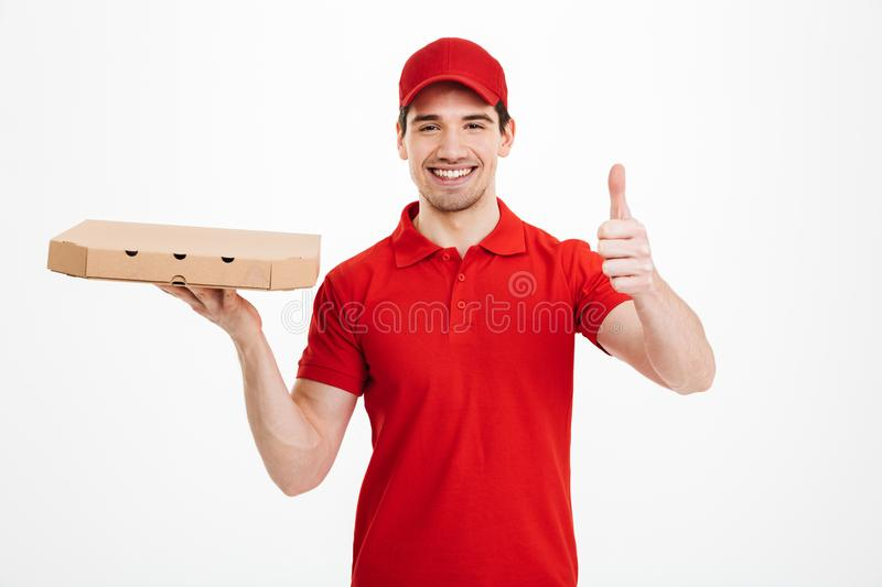 Deliveryman 25y in red t-shirt and cap holding takeaway box with. Pizza and gesturing thumb up over white background royalty free stock photos