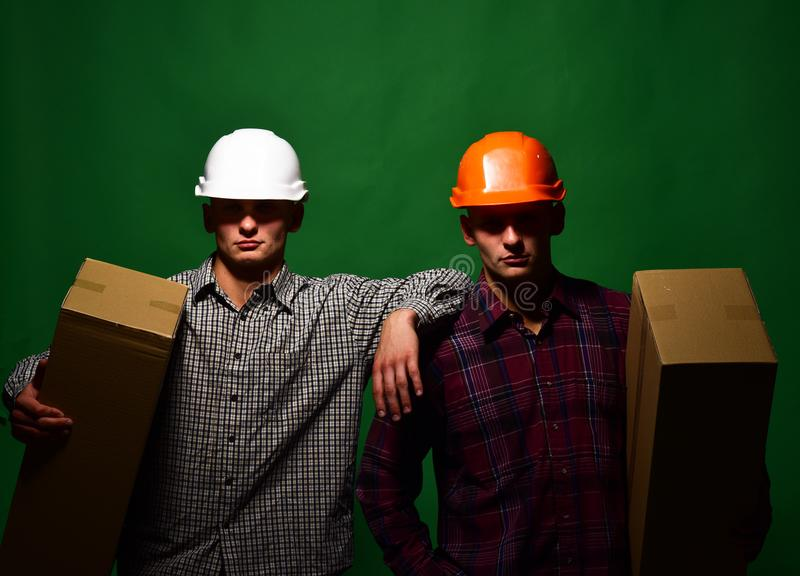 Deliverymen with serious faces easily hold cardboard boxes. In one hand. Twins with helmets move boxes. Delivery and moving concept. Men stand on green stock image