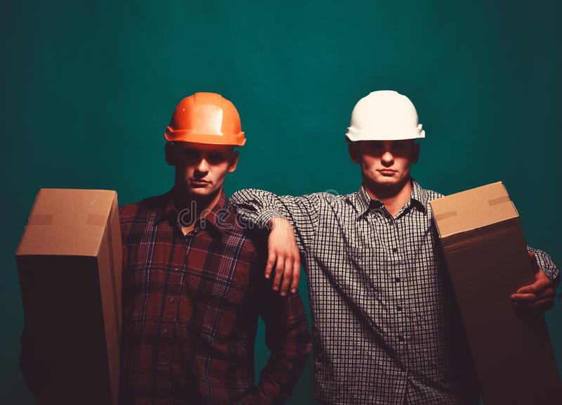 Deliverymen with serious faces easily hold cardboard boxes. In one hand. Twins with helmets move boxes. Delivery and moving concept. Men stand on green royalty free stock photos
