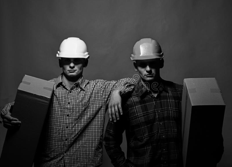 Deliverymen with serious faces easily hold cardboard boxes. In one hand. Twins with helmets move boxes. Delivery and moving concept. Men stand on green royalty free stock images
