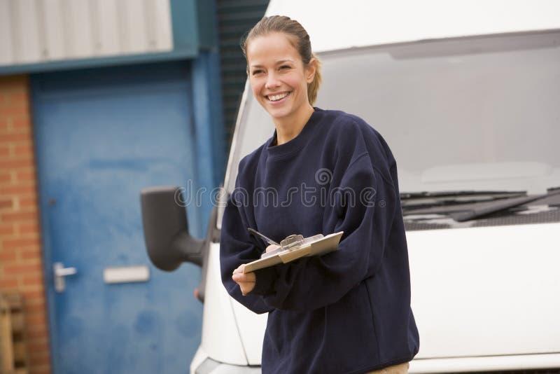 Deliveryperson die zich met bestelwagen het schrijven bevindt royalty-vrije stock afbeeldingen