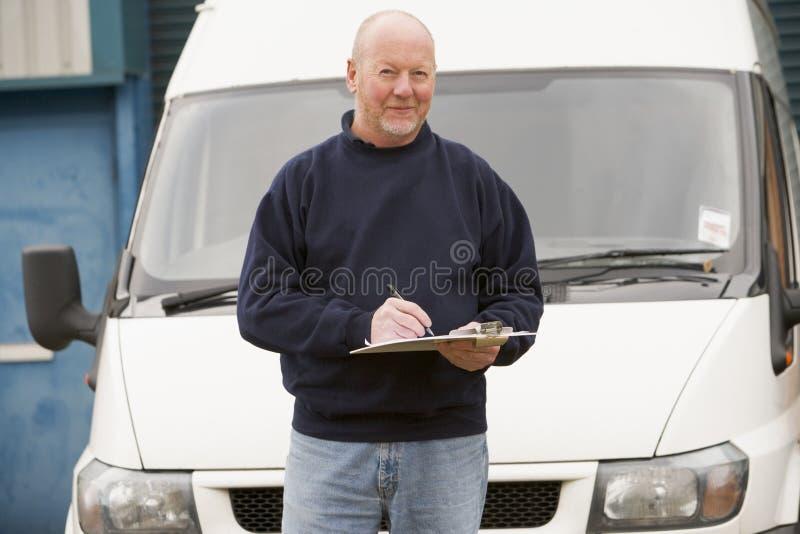 Deliveryperson que se coloca con la furgoneta y la escritura imagen de archivo