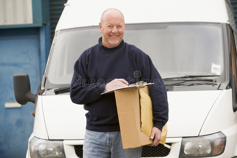Deliveryperson standing with van and box royalty free stock photo