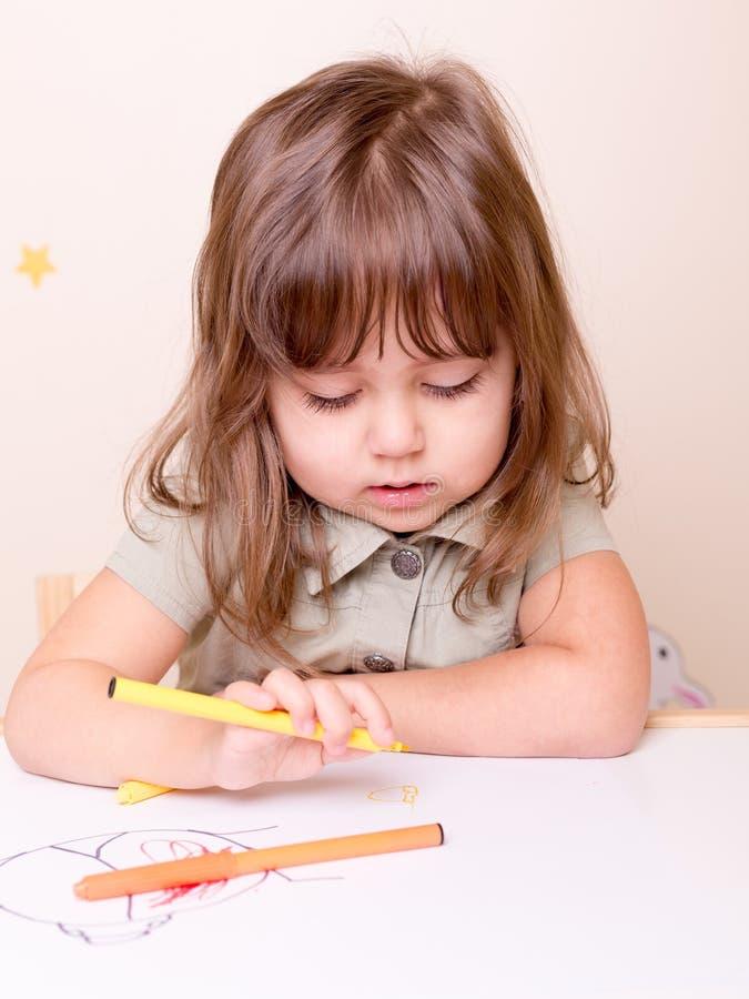 Deliziando ragazza di disegno allo scrittorio nella scuola materna fotografie stock libere da diritti