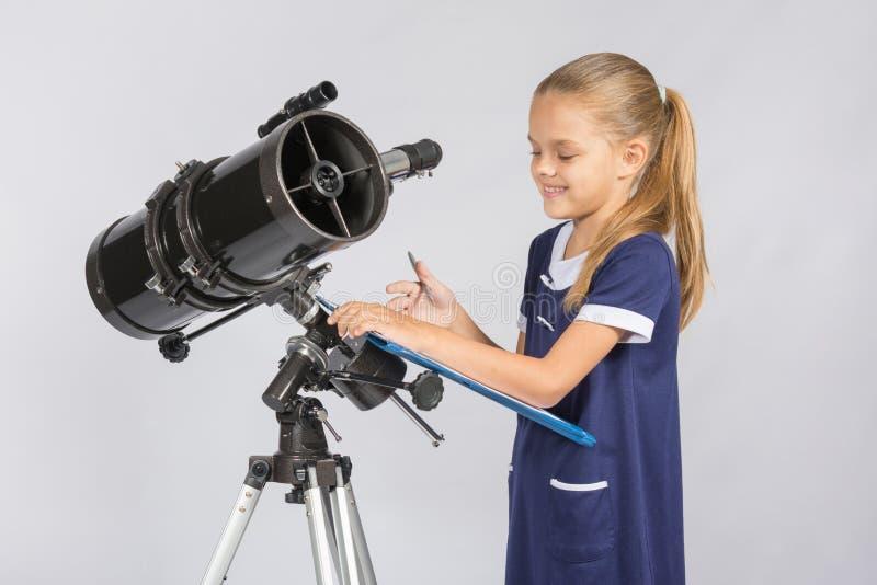 Dell'astronomo annotazioni di sguardi felicemente con le osservazioni immagine stock