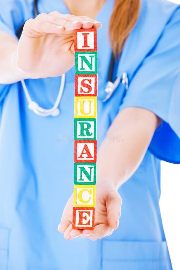 Dell'infermiere di Holding Blocks Spelling assicurazione fuori sopra Backgroun bianco fotografie stock