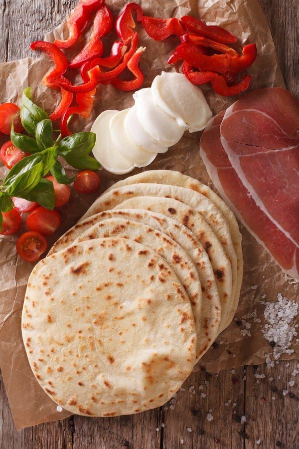 Dell'italiano piadina al forno di recente con il primo piano degli ingredienti Vertica immagine stock