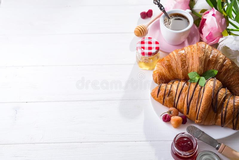 Della prima colazione croissant al forno di recente decorato con inceppamento e cioccolato, fiori sulla tavola di legno in una cu immagine stock libera da diritti