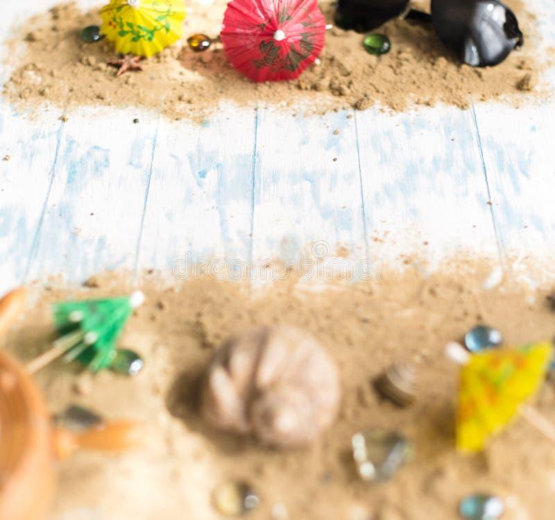 Della spiaggia vita ancora Vetri neri con gli ombrelli del cocktail, conchiglia sulla sabbia su un fondo di legno fotografia stock