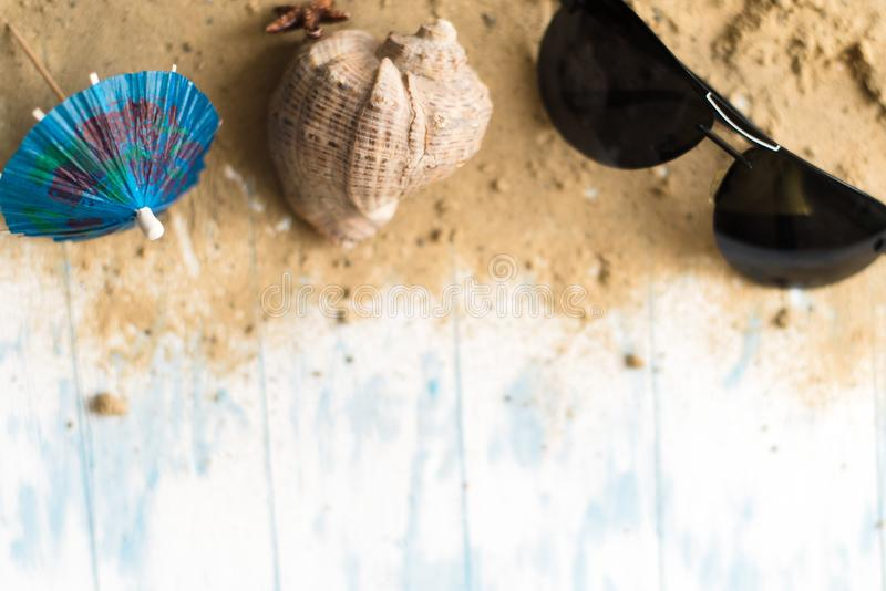 Della spiaggia vita ancora Vetri neri con gli ombrelli del cocktail, conchiglia sulla sabbia su un fondo di legno immagini stock