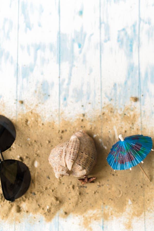 Della spiaggia vita ancora Vetri neri con gli ombrelli del cocktail, conchiglia sulla sabbia su un fondo di legno immagine stock