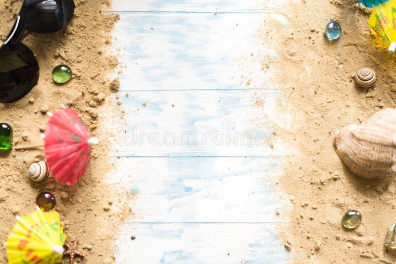 Della spiaggia vita ancora Vetri neri con gli ombrelli del cocktail, conchiglia sulla sabbia su un fondo di legno immagini stock libere da diritti