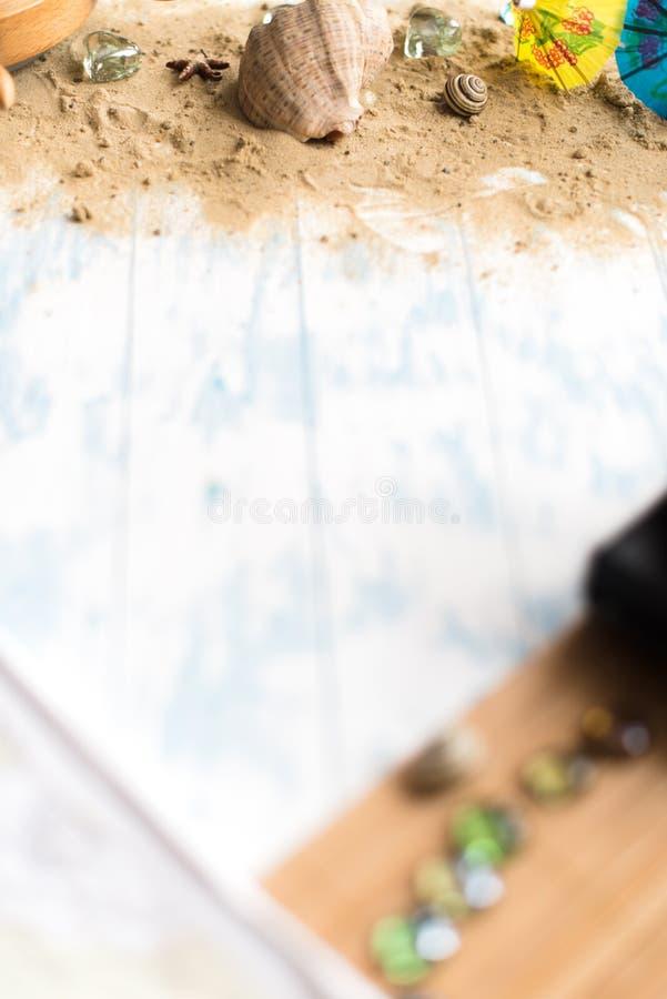 Della spiaggia vita ancora Vetri neri con gli ombrelli del cocktail, conchiglia sulla sabbia su un fondo di legno fotografie stock